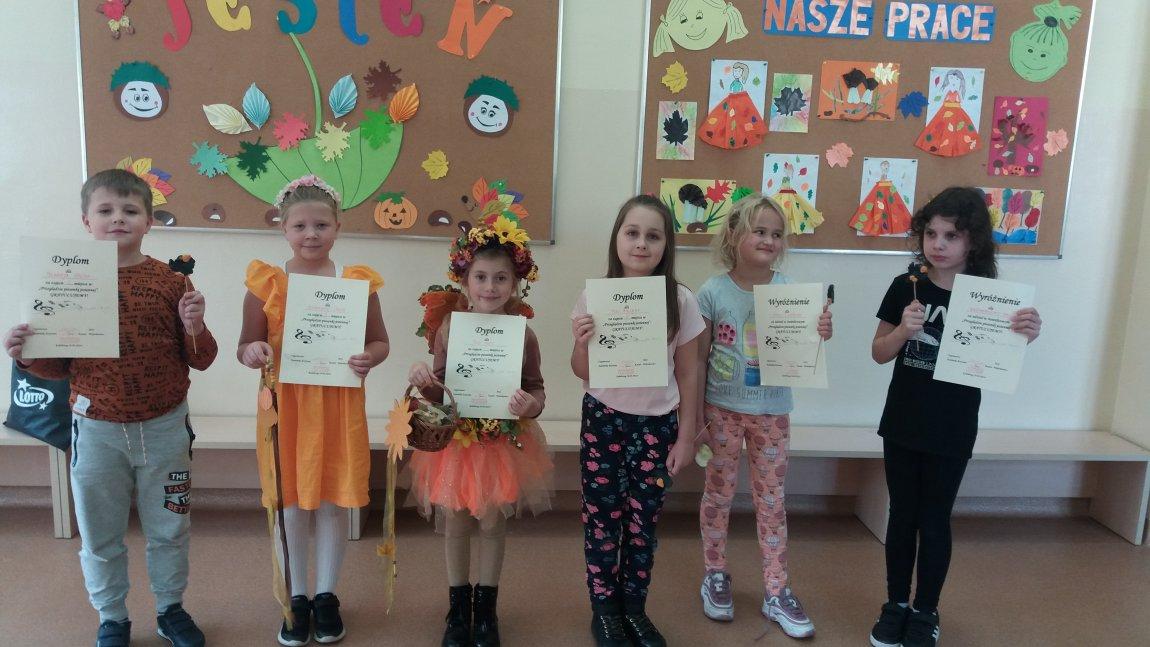 Na zdjęciu dzieci w świetlicy szkolnej z dyplomami za udział w konkursie pioseni jesiennej