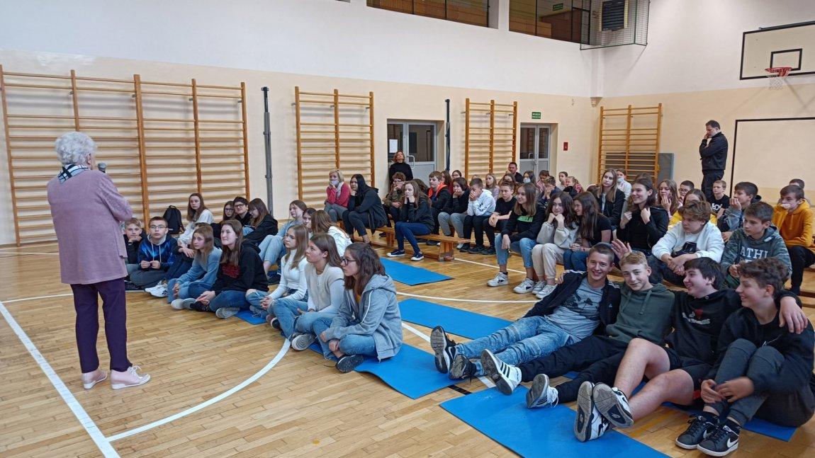 Zdjęcie przedstawia uczniów klas ósmych na sali gimnastycznej podczas spotkania z panią Wandom Przybylską - sybiraczką