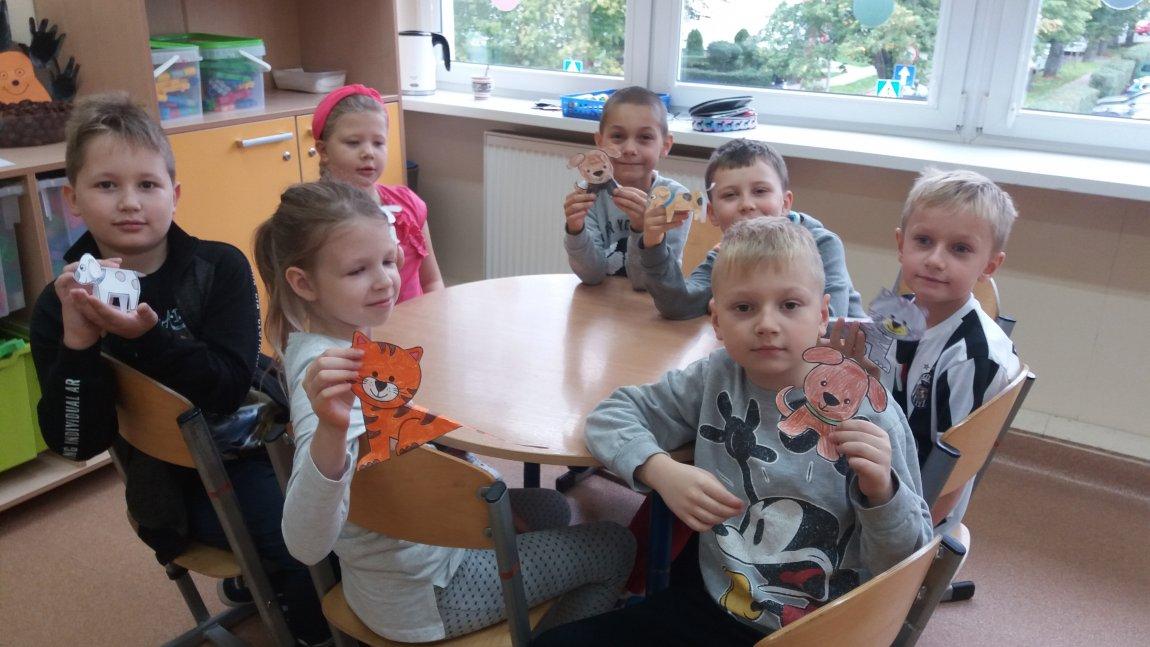 Zdjęcie przedstawia piątkę chłopców i dwie dziewcynki przy stoliku na świetlicy szkolnej. Każde z dzieci trzyma w ręku zwierzątko wycięte z papieru