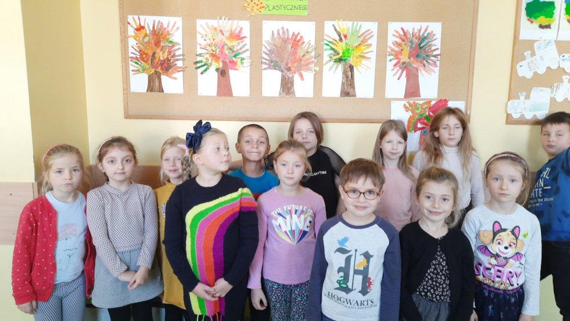 Zdjęcie gromadki dzieci z koła plastycznego stojących koło galerii swoich prac plastycznych