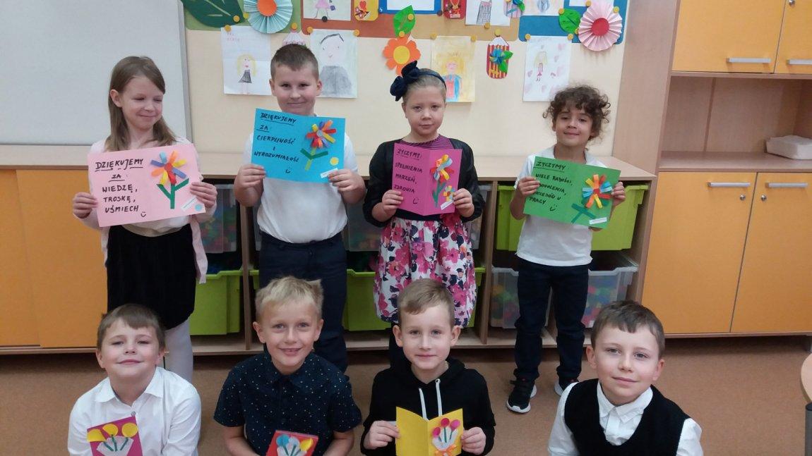 Grafika przedstawia dzieci w świetlicy szkolnej trzymające laurki z życzeniami dla nauczycieli