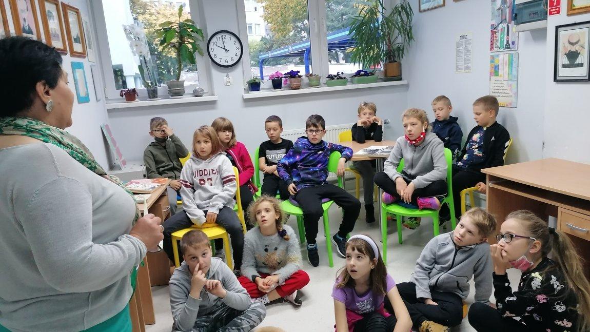Uczniowie oglądają stare książki w bibliotece.