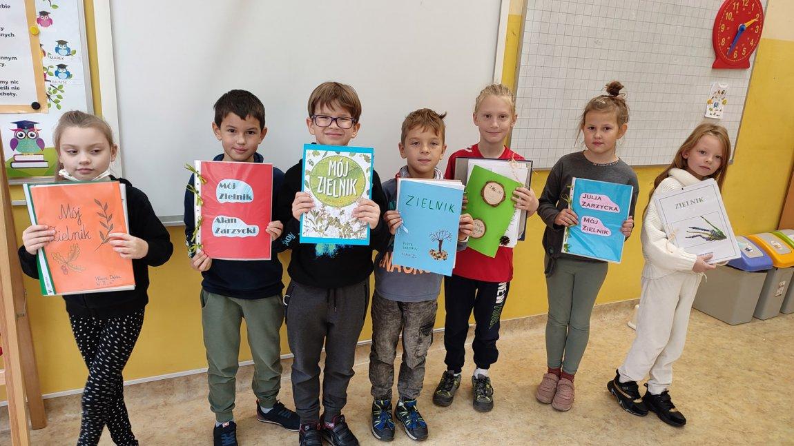 Zdjęcie przedstawia dzieci z klasy 2a z zielnikami w ręku